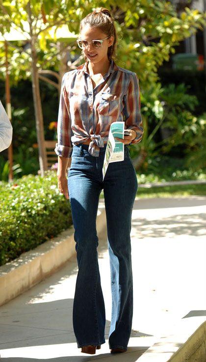 Jessica Alba lleva el pantalones de azul y una camisa de tartán con los tacones negros.La camisa de tartán cuesta ochenta euros, los pantalones cuesta cincuenta dólares,y los tacones cuesta cuarenta y ocho peso.