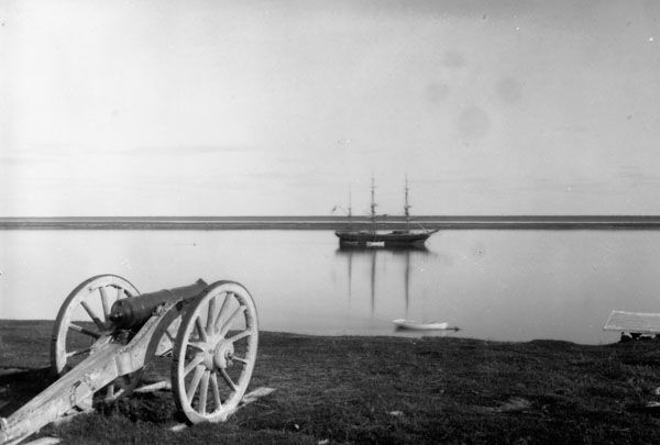 Hayes River at York Factory, Manitoba, Canada. 1880. Cannon in foreground; in far distance a square-rig sailing ship at mouth of Hayes River in Hudson Bay.