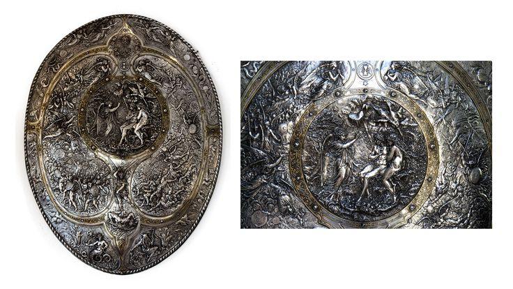 """Milton Shield Su disegno di Morel Ladeuil (incisore francese che aveva lavorato per Napoleone III) che impiegò tre anni per la realizzazione e prodotto da Elkington & co, fu presentato all'esposizione universale di Parigi del 1866 e vinse la medaglia d'oro. Si tratta di una delle prime opere in silver plate e silver plate dorato. Rappresenta la cacciata di Adamo ed Eva dal Paradiso terrestre con riferimento all'opera di John Milton """"Paradise Lost"""". Altezza 85cm Larghezza 66cm."""