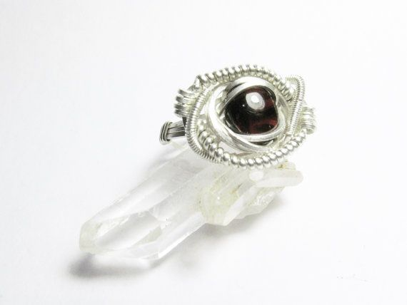 This stunning ring is handmade with a beautiful deep red Garnet. Its made from 925 Sterling Silver wire and is a size 8. I can make custom