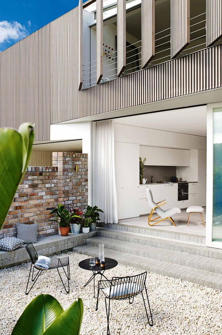 outdoor courtyard pebbles - pebbles and pot plants are great easy-to-maintain options for a courtyard