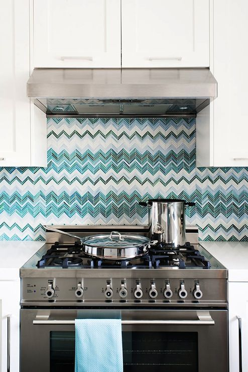 Chic kitchen with white overlay cabinets paired with white quartz countertops and turquoise blue, peacock blue and teal chevron herringbone Missoni style tile kitchen backsplash.