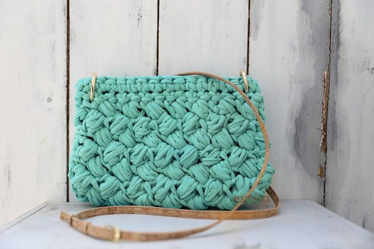Unique weave and beautiful turquoise colour highlight this best-selling bag's summer profile. The softness of 100% cotton yarn in your hands. The long and elegant strap is made by natural cork with gold details. It's length is adjustable with gilded metal fastener. Height 17,50cm Length 27cm Price: 120€