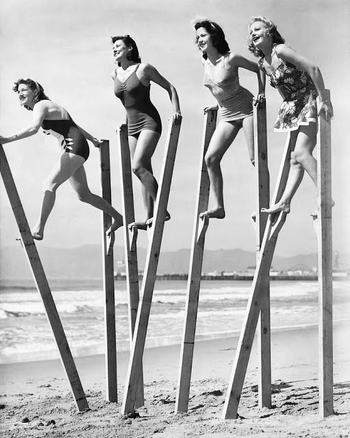 Four women walking on stilts on a sandy beach, c. 1940s. #vintage #summer