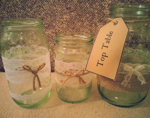 Selection of decorated wedding glass/jam jars using hessian, lace and twine. Some with beeswax candles and some filled with water, dried leaves and an underwater tealight.