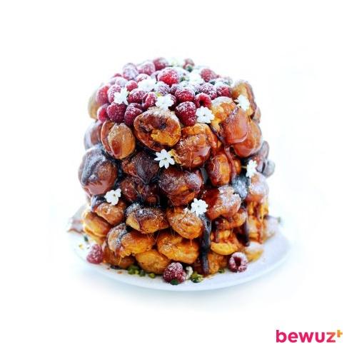 Je kunt ervoor kiezen dit prachtige soesjeskunstwerk van Delicious Magazine helemaal zelf te maken. Je kan het ook anders aanpakken.    Koop 4 pakken (diepvries)soesjes. Leg alle soesjes op een schaal en maak er een soort pyramide van. Smelt chocolade in de magnetron, roer er wat melk door. Giet de chocoladesaus over de soesjes. Versier met frambozen en garneerbloemen.    Da's smart én lekker!  #Bespaar #bewuzt #geldbesparen