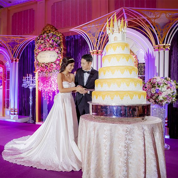 Bride And Groom Cutting Into A Large Five Tier Yellow White Wedding Cake At Hong Kong Disneyland Reception