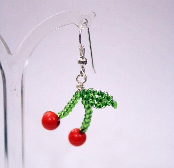 These cute and kitsch cherry earrings have been handmade with love in Brighton.  --------------------------  The stems and leaves are made from green glass beads and the cherries are 5mm red wooden beads.  The fish hooks are hypo-allergic silver wire and the drop is 2.5cm (1 inch).  --------------------------  We send everything by Next Day Courier Service in the UK and by Royal Mail International Tracked for Everywhere Else.  Our Brighton boutique is open 7 days a week, if you would like to…
