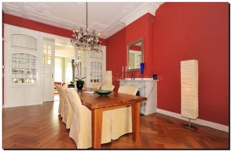 zilveren-spiegel-op-rode-muur-boven-schouw