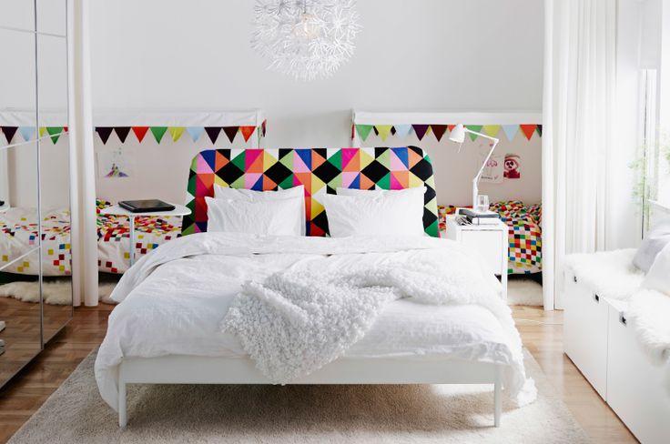 Même pièce. Les rideaux IKEA maintenant ouverts laissent voir deux lits d'enfant derrière le grand lit.