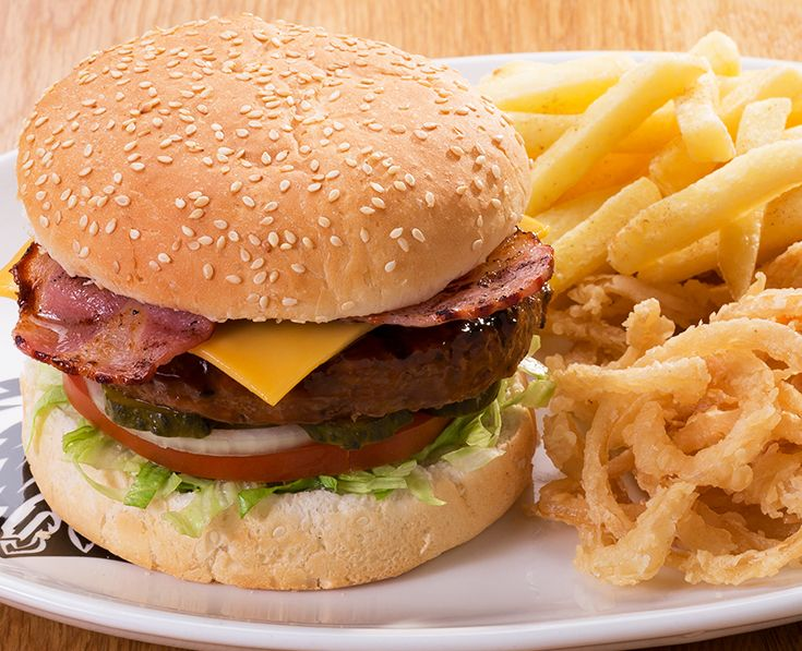 """Cheese and Bacon burger: Tuck into our single or stacked """"cheesy"""" burger - beef, chicken or soya patties served with tomato, onions, gherkins and lettuce. Melted cheese topped with grilled bacon."""