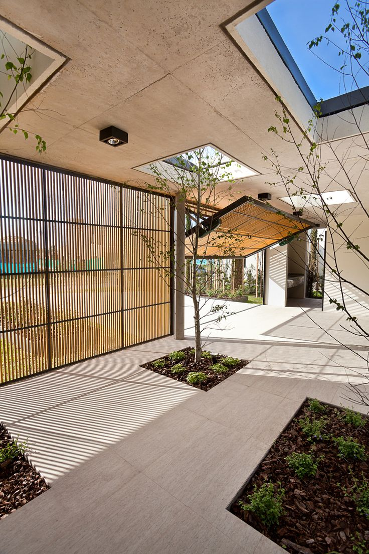 VDV ARQ | Pedro House; timber batten panel-lift door, off-form concrete soffit with cut-out skylights