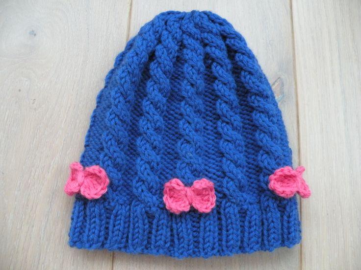 Bonnet bleu à torsades et petits nœuds roses. Blue knitted cable hat. Importé à partir de http://www.tricotemoiunmouton.blogs.marieclaireidees.com