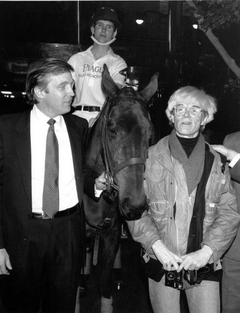 Donald Trump, owner of New York's Trump Tower, holds the bridle of a polo pony while talking to Andy Warhol on Nov. 4, 1983. Yale University polo player Eric Stever sits astride the horse.