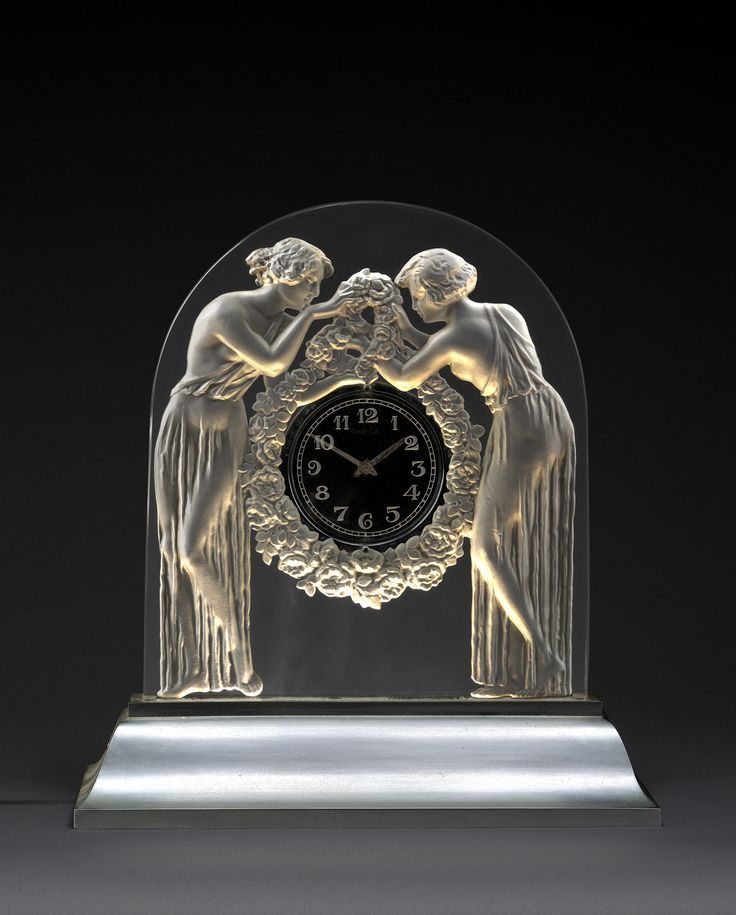 """René Lalique (1860-1945) & Omega - Pendule """"Deux figurines"""", 1926 Verre moulé-pressé incolore sur une base en doucine en métal nickelé, un système d'éclairage électrique dissimulé dans la base (38 cm)"""