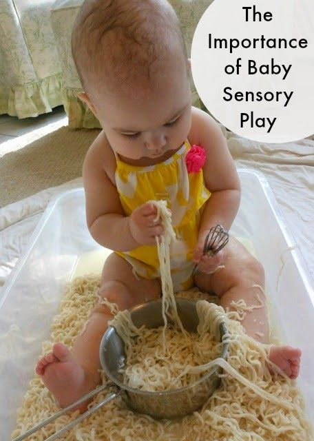 This photo shows a baby exploring sensory play, Learning through play in a tub of spaghetti.