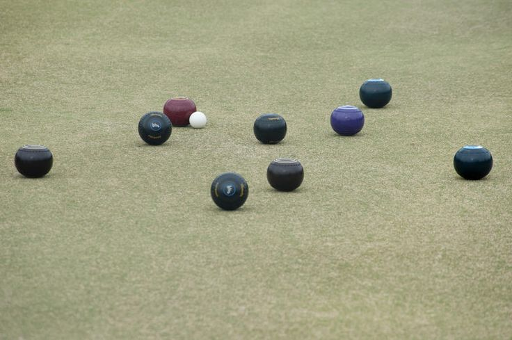 Free Stock Photo: Bowling balls lying around a jack on a bowling green in a game of lawn bowls with copyspace below - By freeimageslive contributor: freebie.photography