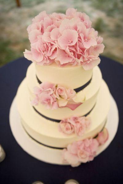 Torta temática de color blanco y negro con flores de color rosa como apliques