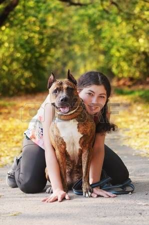 Beautiful young woman with her pit bull dog