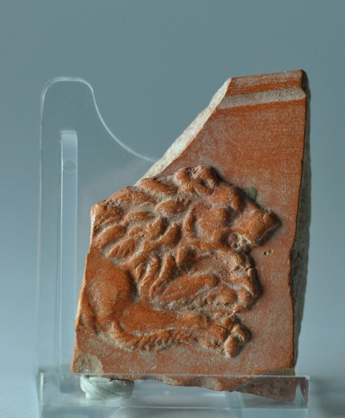 Roman terra sigillata plate fragment with lion, 4th-5th century A.D. African red slip ware plate fragment, North Africa, with lion, 6 cm high. Private collection