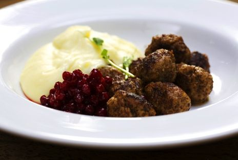 Meatballs served Swedish style with mashed potatoes, brown sauce, lingonberry jam and pickled cucumber.