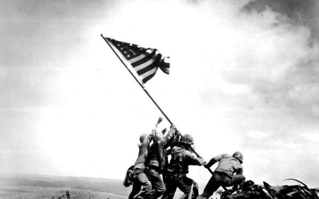 Conoscete la vera storia di questa fotografia? L'immagine dei marines che innalzano la bandiera americana dopo la conquista del più impervio monte di Iwo Jima è una fotografia che ha fatto il giro del mondo e che, per il suo significato iconograf