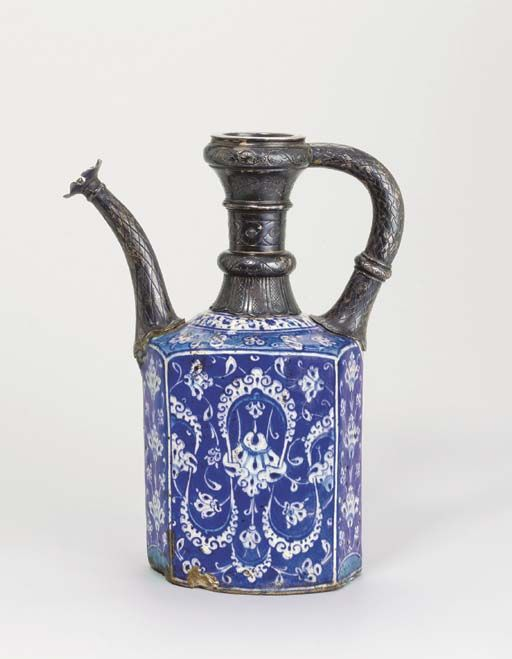 AN IZNIK BLUE, WHITE AND TURQUOISE POTTERY EWER  Ottoman Turkey, circa 1520  The body rising with vertical slightly rounded hexagonal cylindrical sides to the sloping shoulder with raised band before the neck, blue body painted on each of the larger sides with scrolling vine around a large cloudband-motif, smaller sides with stylised flowering plants growing up from a rounded base, turquoise shoulder with similar meandering flowering vine, smaller blue & turquoise vine on a white ground...