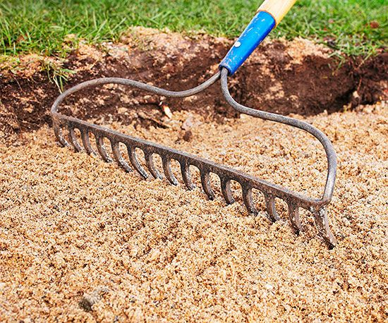 Level a 2-inch layer of builder's sand with a rake. Sand helps with drainage and makes it easier to position the pavers and level the patio.