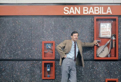 Bob Noorda, the Dutch designer, posing under the San Babila station name. He designed the signage system for the subway in Milan. One of his innovations consists in repeating the name of the station every 5 metres, a feature soon adopted in several cities worldwide.