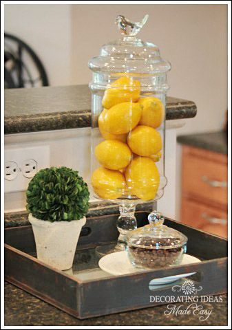 Cute decorating idea for kitchen, glass container (thinking home store here), fill with lemons....thinking you could fill with pumpkins for fall, christmas decorations for Dec., sparkly dollar store Easter eggs for Easter....