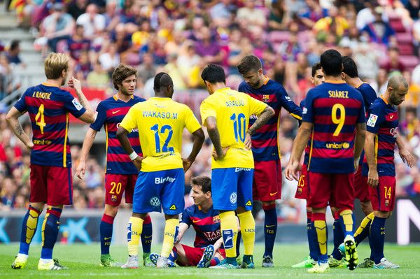 Lionel Messi of FC Barcelona lays injured surrounded by his team-mates and players of UD Las Palmas during the La Liga match between FC Barcelona and UD Las Palmas at Camp Nou on September 26, 2015 in Barcelona, Catalonia.