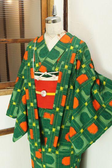 こっくりとした緑に黄色とオレンジが綺麗に映え、曲線と直線が調和した幾何学モチーフとチェックのジオメトリックパターンが織り出されたレトロポップキュートなウールのアンサンブル(羽織と着物のセット)です。