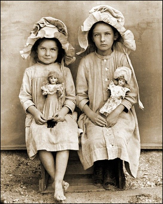Girls with dolls..the girl on the right is deceased.. was common to have photographs of deceased family members as photography was very expensive and this was a way to remember them