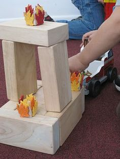 Fire blocks made with dollar store glitter leaves so busy fireman can put out the fire on their block buildings!
