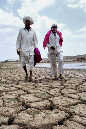 Farmers walk on a parched lake-bed in drought-hit Maan Taluka in Satara, Maharashtra.