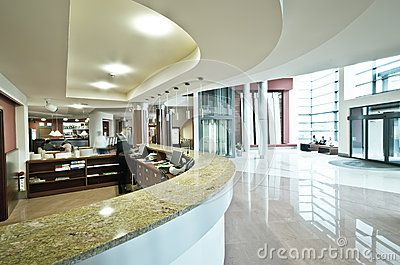Interior of stylish modern hotel showing lobby and curved reception desk.