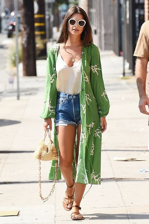 Emily Ratajkowski gives major Cali vibes stepping out in denim cut-offs, white shades and a cool green kimono to top it all off.