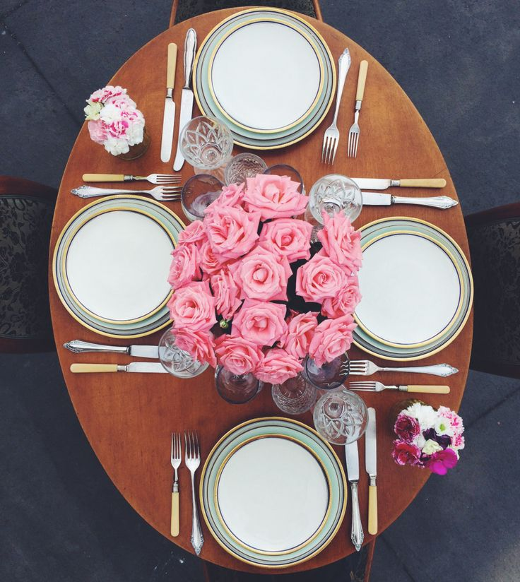 Romantic scenery dinner for four.  Pink roses bouquet, vintage cutlery. Romantic tabletop. Vintage, Bavaria porcelain plates and cristal glasses. Outdoor dinner.