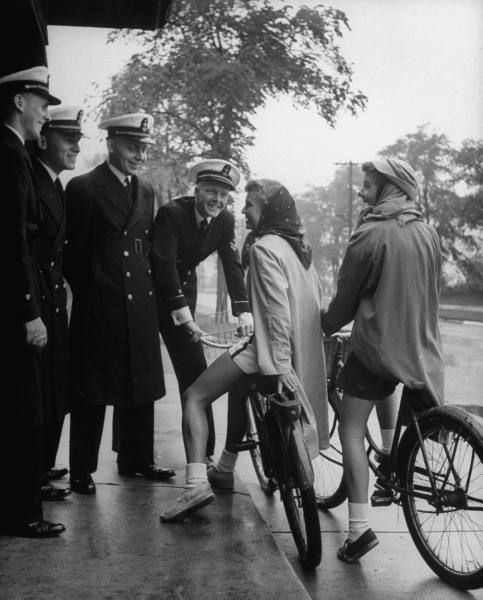 College girls on bicycles stopping to chat with cadets. Photograph by Nina Leen. New London, Connecticut, 1945.
