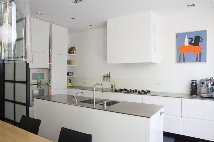 Moderne witte keuken van Paul van de Kooi. Deze moderne witte keuken past in elk modern interieur. Opvallend zijn de gaspitten die los in het aanrechtblad zijn verwerkt in plaats van in een kookplaat. Zo bepaal je zelf hoeveel ruimte jij voor je pannen nodig hebt. Het spoeleiland heeft een roestvrijstalen aanrechtblad met geïntegreerde anderhalve spoelbak. Dit zorgt voor veel schoonmaakgemak. Daarnaast is er gekozen voor een kokendwaterkraan.