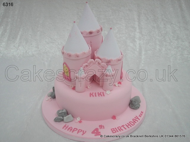 Fairy Castle Cake. All girlie pink fairy princess castle birthday cake complete with three cake turrets. Decorated with simple pink and white flowers and each tower window has an edible photo/image of your choice