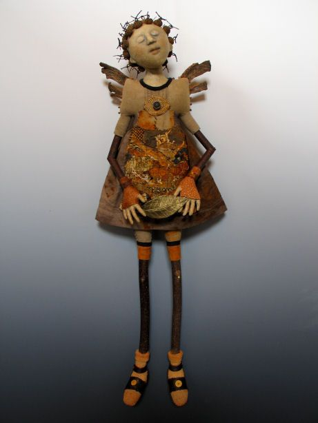 """Angel with Gilded Leaf  Flax paper over cloth face & hands, Poplar branch arms & legs, Natraj wings, leather shoes & leaf, beads, found metal, acorn cap & wire hair, colored pencil, acrylic paint, metallic rubs;  25"""" h x 8""""w x 4""""d @ akirastudios.com"""