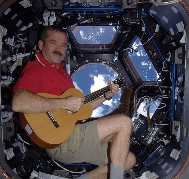 Canadian astronaut Chris Hadfield strums a guitar while gazing at the Earth from the International Space Station in December 2012.