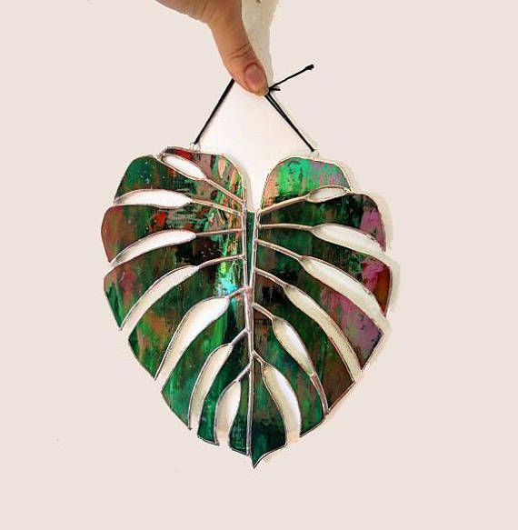 This monstera leaf suncatcher was designed by me and made with my own two hands using the copper foil method of stained glass. This leaf is life-sized and the pattern was built off an actual leaf for ultimate authenticity. Made with a dark green semi-opaque swirled glass with an