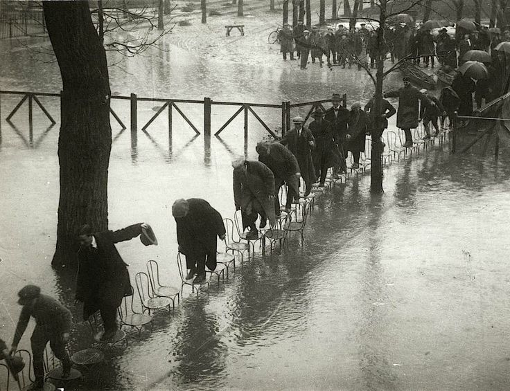 People walking on the chairs at the Maisons-Laffitte racecourse to escape the river Seine flood. Paris. 1924.