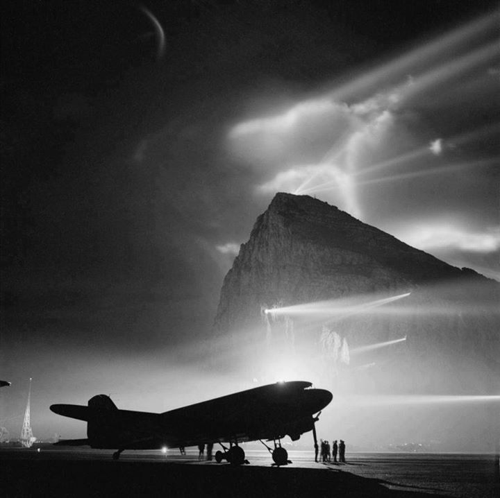 During World War II a Douglas Dakota of BOAC is silhouetted at Gibraltar by the batteries of searchlights on the Rock as crews prepare it for a night flight to the United Kingdom