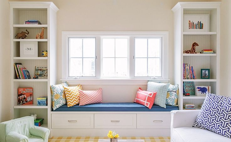 source: Lauren Nelson Design Gorgeous girls bedroom with built-in bookshelves flanking window seat with drawer storage. The floor is layered with a yellow and white gingham rug. In the foreground you can catch a glimpse of a white chair topped with a geometric patterned blue and white pillow.