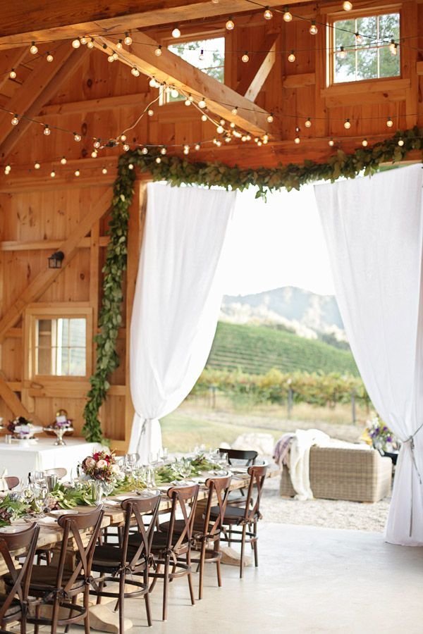 Beautiful barn wedding with garland and curtains at the entrance and white globe string lights