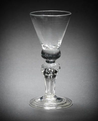 A very rare moulded-stem Royal commemorative wine glass, circa 1714 - The thistle-shaped bowl solid at the base, set on a short plain section above a four-sided teared stem moulded with four crowns to the shoulders and a diamond on each side, over a conical folded foot, 15.4cm high