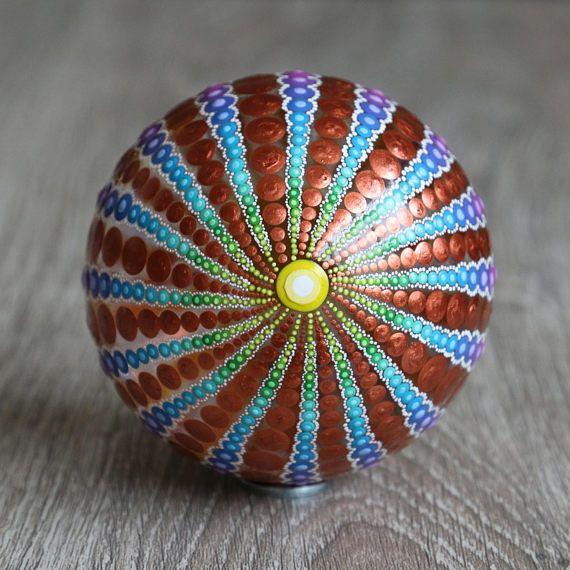 Mandala bal beschilderd met regenboog kleuren en koperkleurige acrylverf. De diameter van de bal is ongeveer 8 cm. De bal is gemaakt van helder glas en afgewerkt met glanzende vernis. Maar kan alsnog niet gebruikt worden voor buiten, etc. Op de vierde foto is als voorbeeld te zien hoe de mandala bal verpakt is in een organza zakje met een metalen ringetje (waar de bal opgeplaatst kan worden). Leuk om dus kado te geven! Bijvoorbeeld voor een huwelijk, housewarming, geboorte of yoga leraar…